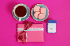 Coffee with macarons and ring on a pink background. An offer of marriage. Top view, toned image. Coffee with macarons and ring on a pink background . An offer of Royalty Free Stock Photography