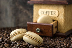 Coffee macaroons and coffee grinder. Coffee macaroons, coffee grinder and wooden table background Royalty Free Stock Photography