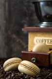 Coffee macaroons and coffee grinder. Coffee macaroons, coffee grinder and wooden table background Stock Image
