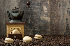 Coffee macaroons and coffee grinder. Coffee macaroons, coffee grinder and wooden table background Royalty Free Stock Photos