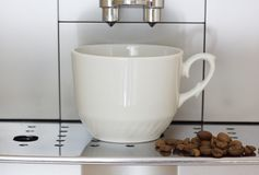 Coffee machine brews coffee. The coffee machine brews coffee and pours it into mugs Royalty Free Stock Photos