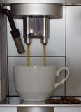 Coffee machine brews coffee. The coffee machine brews coffee and pours it into mugs Royalty Free Stock Photography