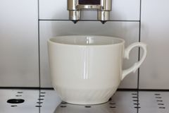 Coffee machine brews coffee. The coffee machine brews coffee and pours it into mugs Stock Photos
