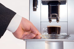 Coffee machine with coffee cup closeup. Closeup hand takes a cup of coffee from the coffee machine Stock Photography