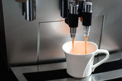 Coffee machine and a cup of coffee. Close up of espresso coffee machine dispensing coffee into a coffee cup Stock Image