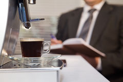Coffee machine with cup of hot espresso in office. Businessman decided to use coffee without leaving the office Royalty Free Stock Photos