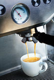 Coffee machine dispensing coffee. Automatic filter coffee machine dispensing a cup of delicious hot frothy aromatic coffee into a white ceramic cup in a catering Stock Images