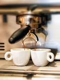 Coffee machine dispensing a double espresso. Coffee machine dispensing a double Italian espresso into two small cups in a coffee house or restaurant Stock Images