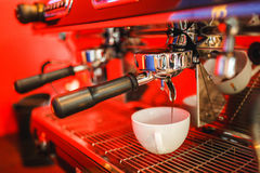Coffee machine makes two coffee on red background. Coffee machine makes coffee on red background Royalty Free Stock Image