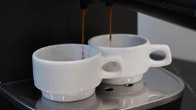 Coffee Machine making coffee. Close up view of coffee machine preparing espresso in white cups. Black coffee espresso pouring into stock footage