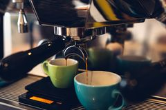 Coffee machine pouring coffee into a two colored cups stock images