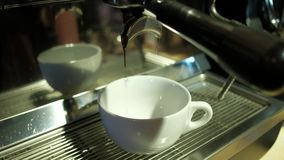Coffee machine pouring espresso in cup. Coffee pouring into a two white porcelain cups from coffee machine in 4k stock footage