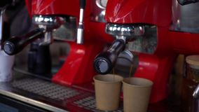Coffee machine pouring coffee in to the paper cups. stock footage
