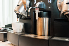 Coffee machine pouring into white cup Stock Photos