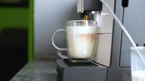 A coffee machine pours espresso into a glass cup with milk.
