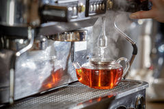 Coffee machine pours hot water into the teapot. Royalty Free Stock Images