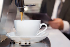 Coffee machine prepares fragrant espresso. Businessman prepares espresso by means coffee machine Royalty Free Stock Photography
