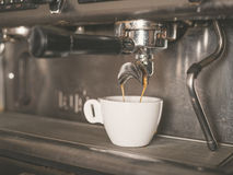 Coffee machine and a small white cup Royalty Free Stock Image