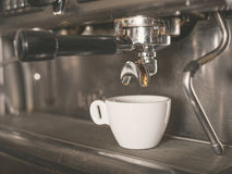 Coffee machine and a small white cup Stock Image