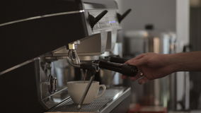 Coffee machine in use: hot coffee pouring into white cup, close-up. Coffee machine in use: hot coffee pouring into cup and then male hand pushing the button to stock footage