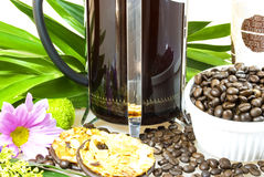 Coffee maker. Made of glass with metallic lid, decorated with flowers, leaves, biscuits and coffee beans Stock Image