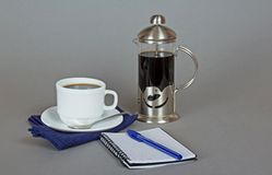 Coffee maker and a ballpen with note book Stock Photo
