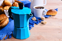 Coffee maker. Blue color on the background of croissants and utensils for coffee Royalty Free Stock Photography