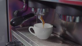 Coffee maker and cup. Cappuccino from coffeemachine slowly pouring in a single white cup, freshly brewed coffee. Making coffee in a coffee maker in cafe stock video footage