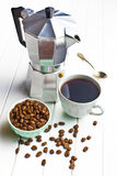 Coffee maker with cup of coffee and coffee beans. On wooden background Royalty Free Stock Photo