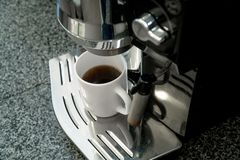Coffee maker with the cup of coffee in a kitchen royalty free stock photos