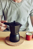 Coffee maker and cup. From metal with coffee and men torso behind Stock Photo
