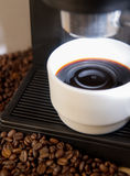 Coffee maker machine with white coffee cup. Close up coffee maker machine with white coffee cup and coffe bean Stock Photo