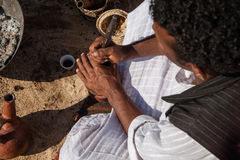Coffee Maker. Marsa Alam, Red Sea/ Egypt – OCTOBER 31: unidentified Bedouin young man from Bishari Tribe drinks fresh Bedouin coffee called gabana in Royalty Free Stock Photo