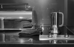 Coffee Maker On Stove. Coffee maker and toaster on a kitchen stove, indoor shot in black and white Stock Photo
