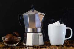 Coffee maker, white cup of coffee and dessert stock photos