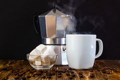 Coffee composition - coffee maker, white cup of coffee and dessert royalty free stock photo