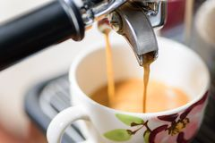 Hot coffee flowing into a cup. Coffee making, hot coffee flowing into a cup from espresso machine Stock Photo