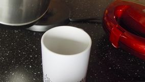 Coffee making in white cup on black table. Add two sugar cubes, one teaspoon of instant coffee and pouring a hot water from a kett stock video