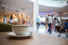 Coffee in mall. Coffee cup on cafe table in commercial center mall interior Stock Photography