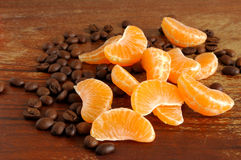 Coffee and Mandarin. Tangerine and coffee beans on a wooden background Royalty Free Stock Photo