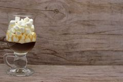 Coffee And Many Small Marshmallows In A Transparent Glass Cup On A Wooden Background. The Photo In Warm Colors stock images
