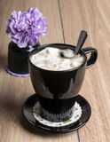 Coffee with marshmallows in a black mug and flower Stock Photos