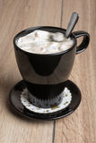 Coffee with marshmallows in a black mug Royalty Free Stock Photography