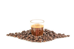 Coffee in measuring cup and coffee beans on the white background Stock Photos
