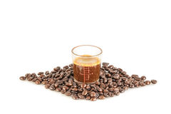 Coffee in measuring cup and coffee beans on the white background Royalty Free Stock Photo