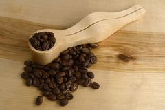 Coffee measuring spoon and coffee beans on a wooden board Stock Images