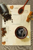 Coffee menu, cup with espressoo coffee, spices and other ingredi. Coffee cup stands on the menu with different spices and ingredients - vertical top view royalty free stock photography
