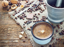 Coffee in a metal mug on the old wooden background with grains Stock Photo