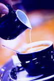 Coffee with milk. Pouring milk in coffee in blue tone Royalty Free Stock Images