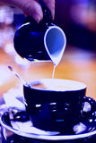 Coffee with milk. Pouring milk in coffee in blue tone Stock Images